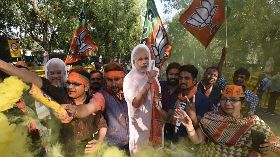 BJP workers celebrate outside the party headquarters in New Delhi on Sunday.