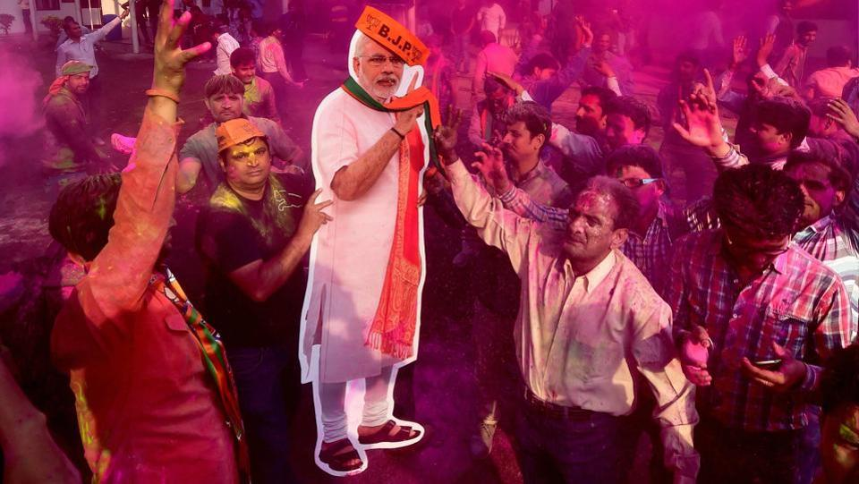 BJP workers play Holi with a giant cut-out of Prime Minister Narendra Modi as they celebrate the party's victory. (Manvender Vashist / PTI)