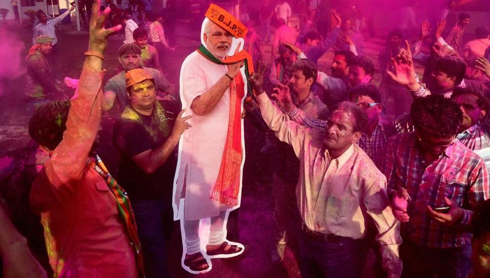 BJP workers play Holi with a giant cut-out of Prime Minister Narendra Modi as they celebrate the party's victory in the UP and Uttarakhand assembly elections, at the party headquarters in New Delhi on Saturday.