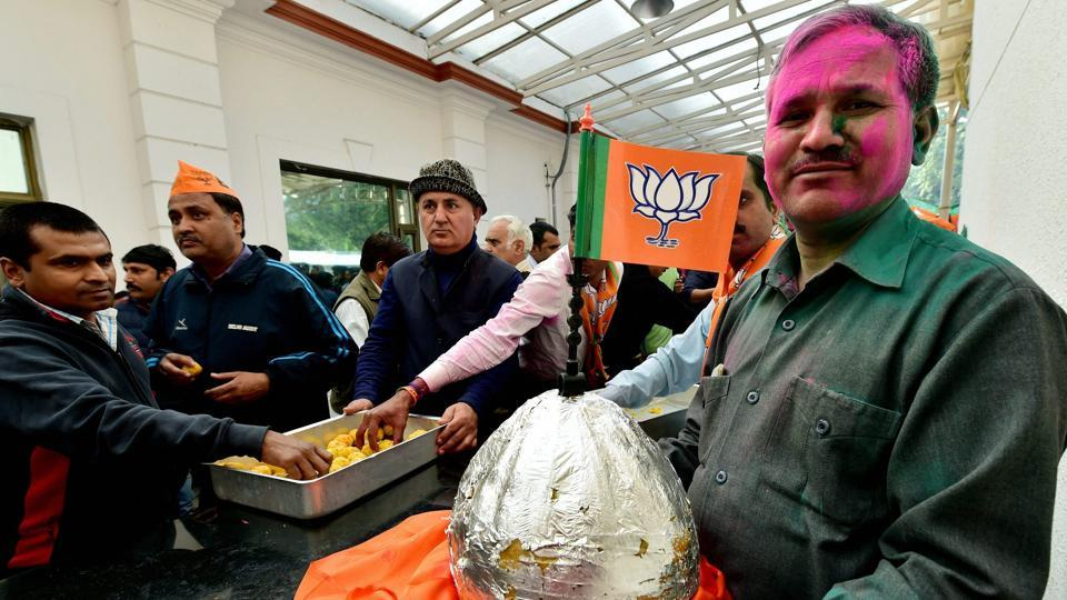 A BJP worker holds a huge laddu during celebrations after the party's victory in UP and Uttarakhand assembly elections, at the party headquarters in New Delhi on Saturday.