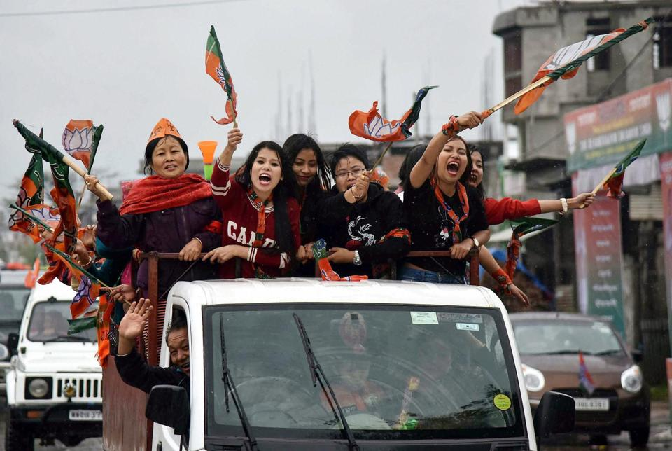 Supporters of BJP wave their flags as they celebrate their candidate win.The multi-phase elections across India, which began in February, ended on Wednesday, with results announced on March 11. (PTI)