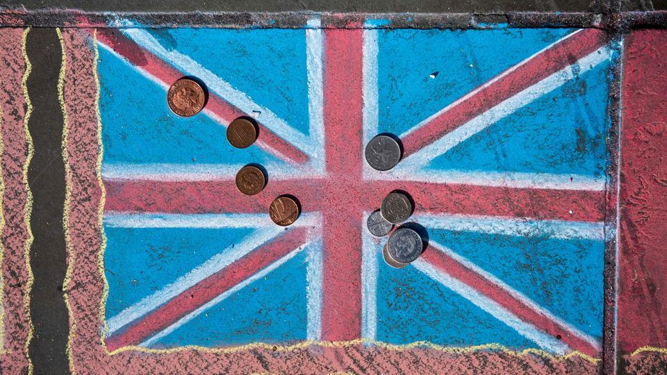 Pound sterling coins are pictured on a chalk drawing of a Union flag on the pavement in Trafalgar Square in London.