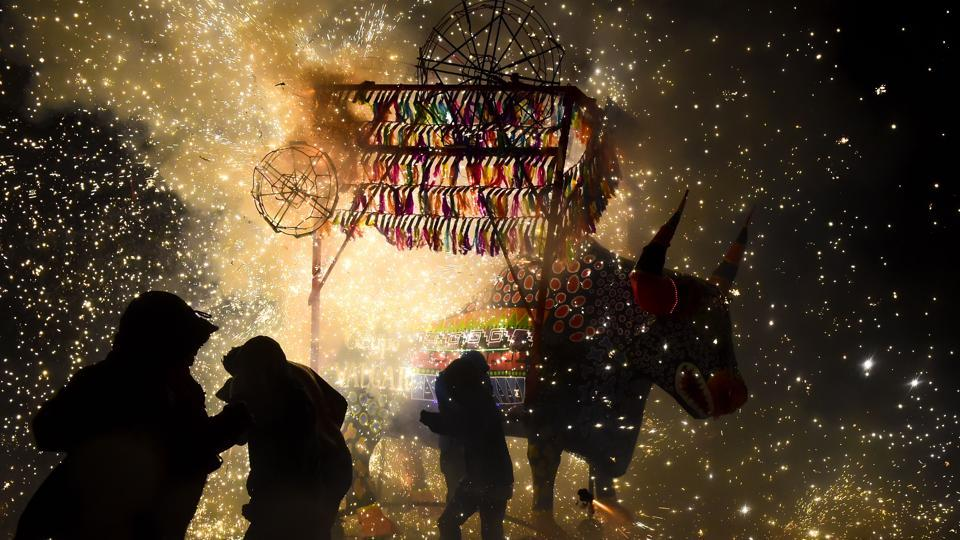 People run away from fireworks exploding around them next to a traditional 'torito' (little bull) -bull made of paper, wood and fireworks- during the celebration of San Juan de Dios festivity in Tultepec, in the outskirts of Mexico City . (RONALDO SCHEMIDT / AFP)