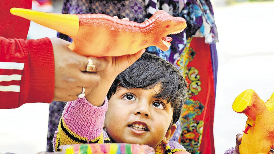 A child looks at a water gun for Holi at Indra Market. Many markets inNoida were buzzing with shoppers of all ages a day before Holi.