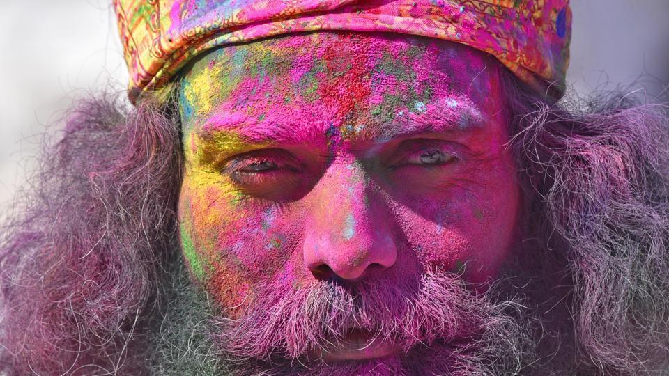A Hindu devotee  covered in coloured powder  stands outside  the Durgiana Temple . (Gurpreet Singh / HT photo)
