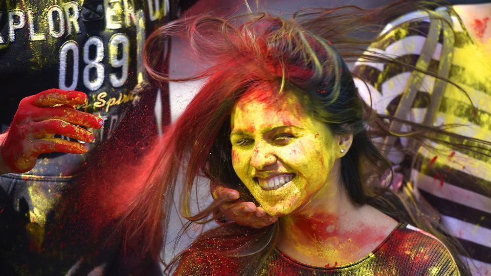 People smear colored powder on the face of a girl as they celebrate Hol in New Delhi.  Celebrants light bonfires, throw colourful powder called gulal, eat sweets, and dance to traditional folk music. (Raj K Raj/HT PHOTO)