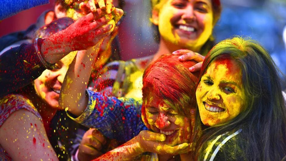 A college student reacts as coloured powder is thrown into her face during Holi in New Delhi. (Raj K Raj/HT PHOTO)