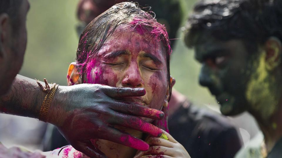 A woman shuts her eyes as coloured powder is smeared on her face during  Holi celebration in Guwahati.  (Anupam Nath / AP)