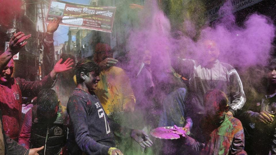 Dance and throw coloured powder during Holi celebrations in Jammu on Sunday.
