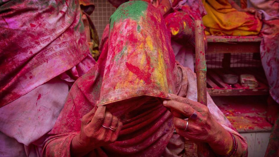 A widow smeared with colours covers her face during Holi celebrations, the arrival of spring festival, at the Gopinath temple in Vrindavan. (Manish Swarup / AP)