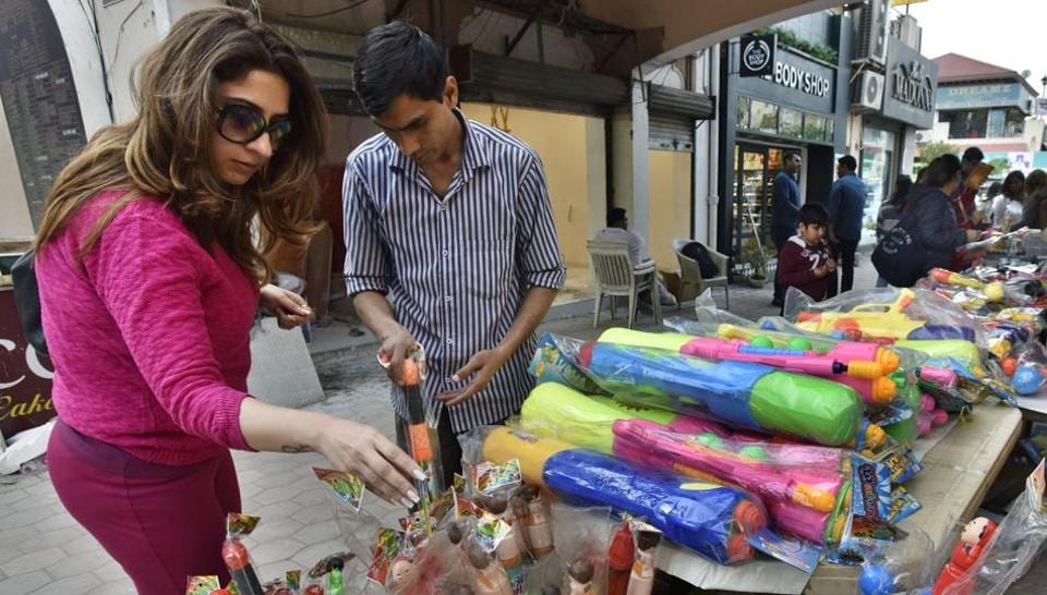 Residents shop for Holi at Gurgaon's Galleria market on Sunday.