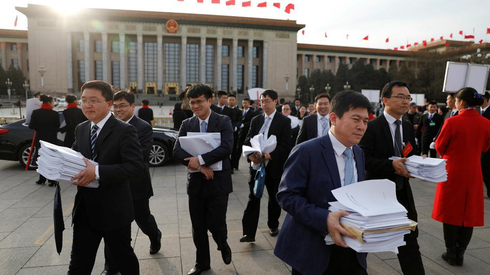 People carry stacks of papers near the Great Hall of the People after a plenary session of the Chinese People's Political Consultative Conference (CPPCC) in Beijing, China, March 11, 2017.