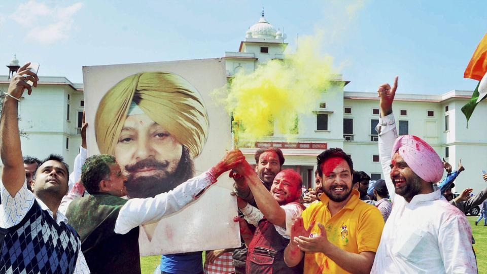 Congress workers celebrate with a poster of Captain Amarinder Singh  outside his residence in Patiala on Saturday.
