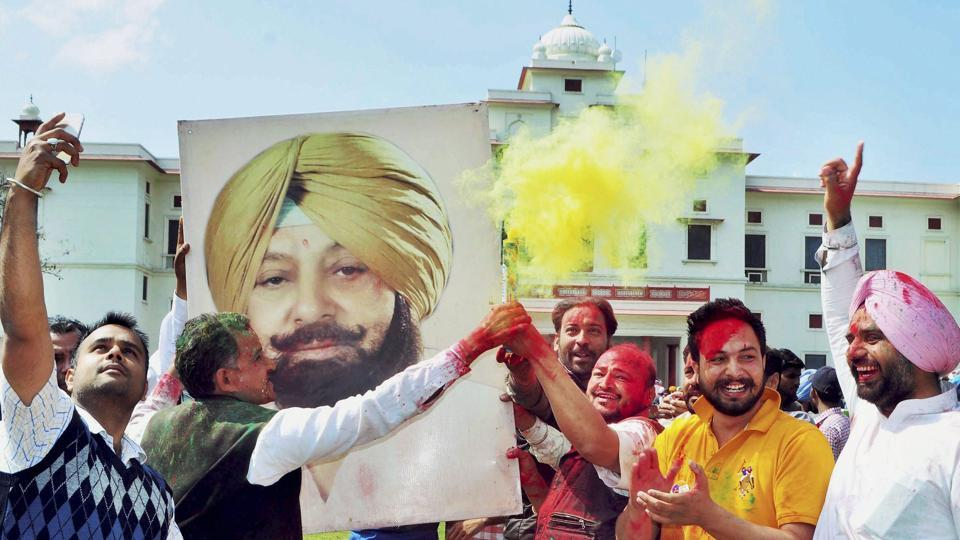 Congress workers celebrate with a poster of Amarinder Singh after the party's thumping victory in the state assembly polls in Patiala on Saturday.