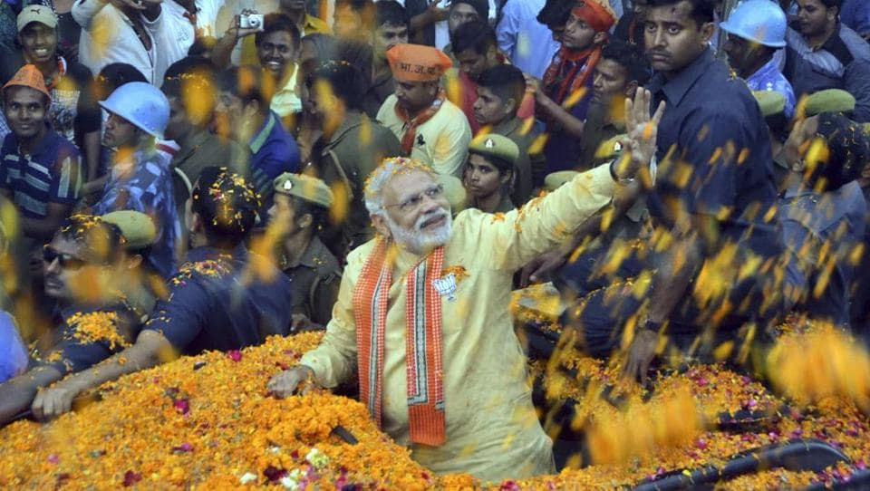 Prime Minister Narendra Modi waves to people during a road show in Varanasi.