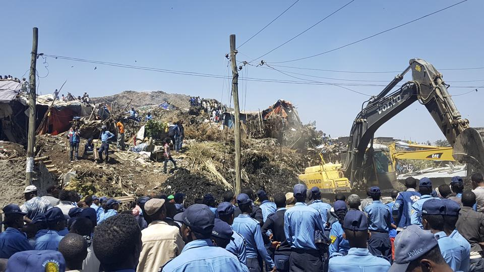 Police officers secure the perimeter at the scene of a garbage landslide.