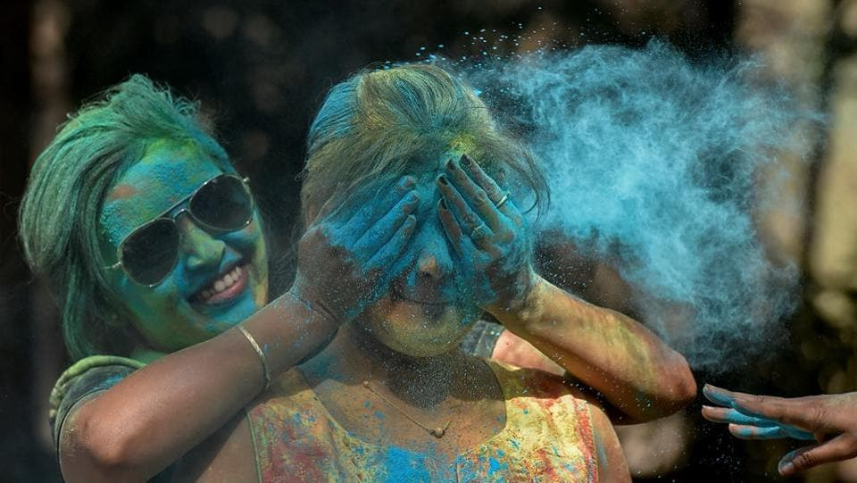 A Mumbaiite applies coloured powder on her friend at Shivaji Park. (Kunal Patil/HT Photo)