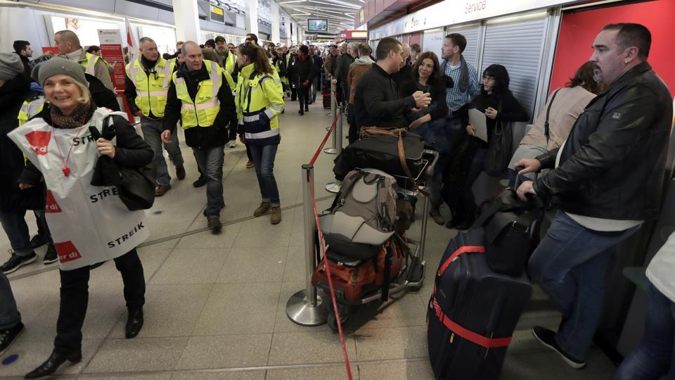 Participants of a strike walk past travellers queuing in front of a booking change counter at the Tegel airport in Berlin.