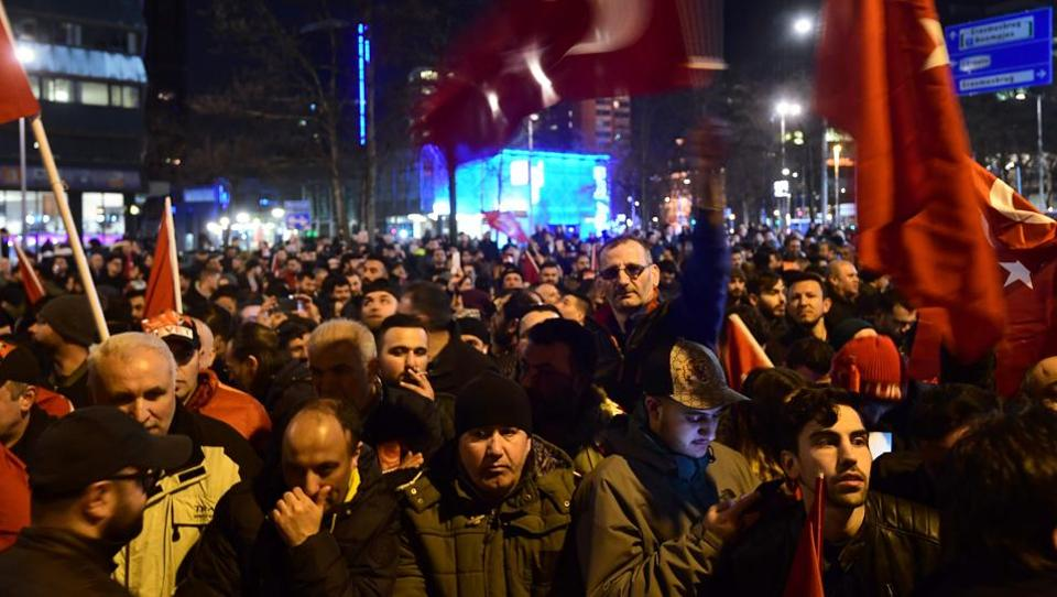 Turkish residents in the Netherlands wave Turkey's national flags as they take part in a gathering outside Turkey's consulate in Rotterdam.