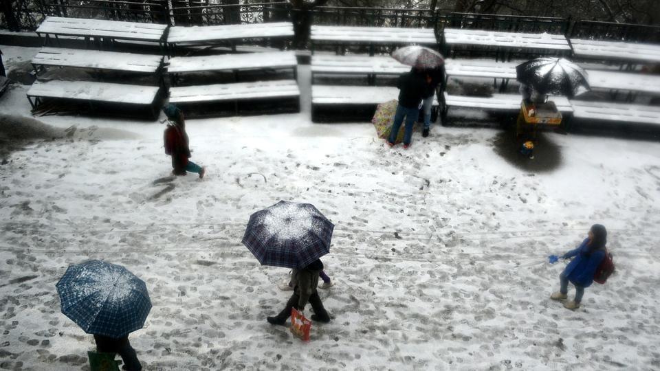People walking with umbrellas during snowfall at Lakkar Bazaar, Shimla.