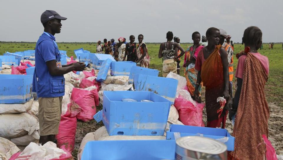 People collect food assistance on the outskirts of Mayom in South Sudan. South Sudanese rebels have kidnapped eight locals working for US charity Samaritan's Purse.