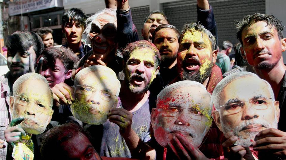 Youth BJP supporters carrying PM Modi's masks during Holi celebrations in Jammu on Sunday.