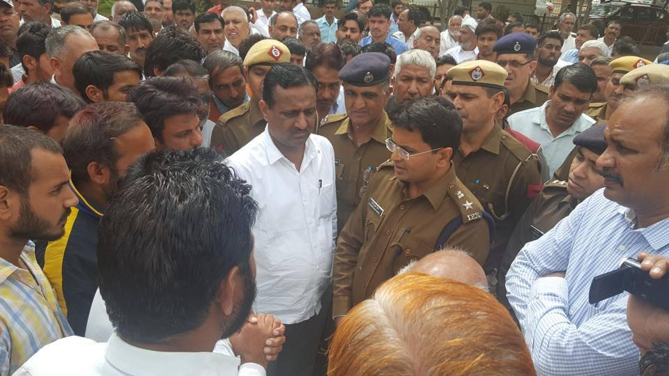 Police discuss with agitated people in Sekhpura village of Haryana's Hisar district.