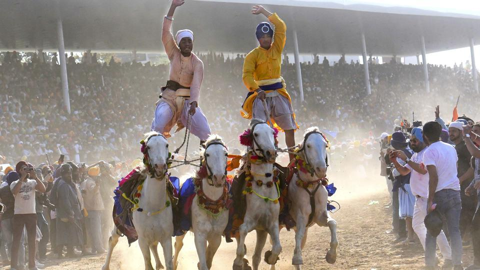 Nihangs, Sikh men who belongs to an armed Sikh order, display horse riding skills during the Hola Mohalla celebrations in Anandpur Sahib on Monday. Hola Mohalla is a Sikh festival that takes place on the day following Holi, the festival of colours. (Sanjeev Sharma/HT Photo)