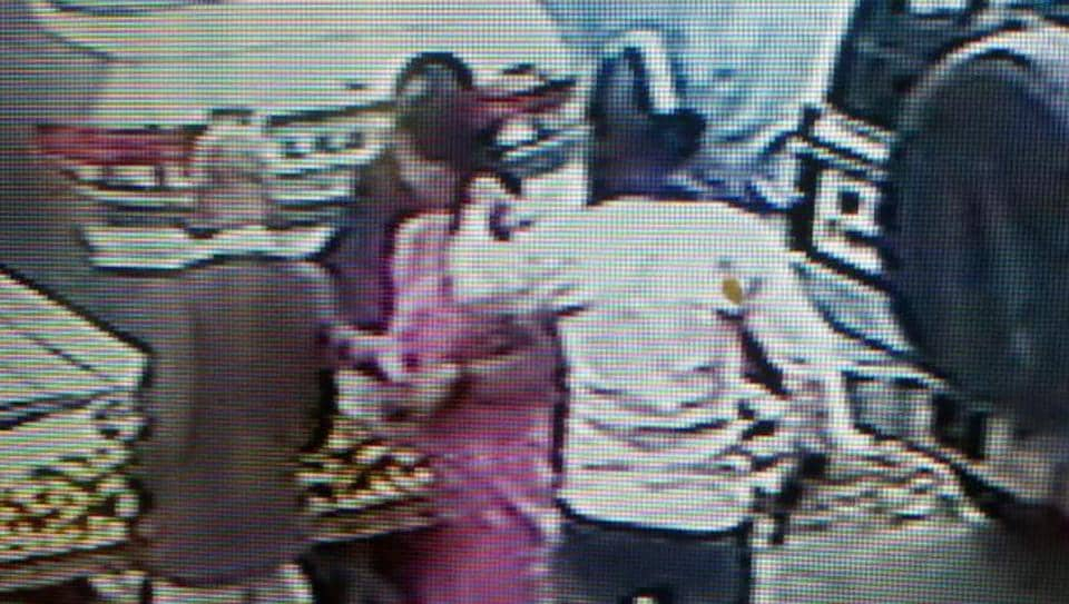 CCTV footage shows the robber, with a helmet covering his face, raise his pistol up to the woman in the market.