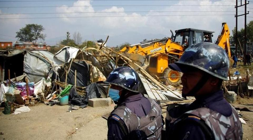 Nepalese police personnel stand guard as makeshift shelters are being demolished at the displacement camp for earthquake victims at Chuchepati in Kathmandu, Nepal on March 14.