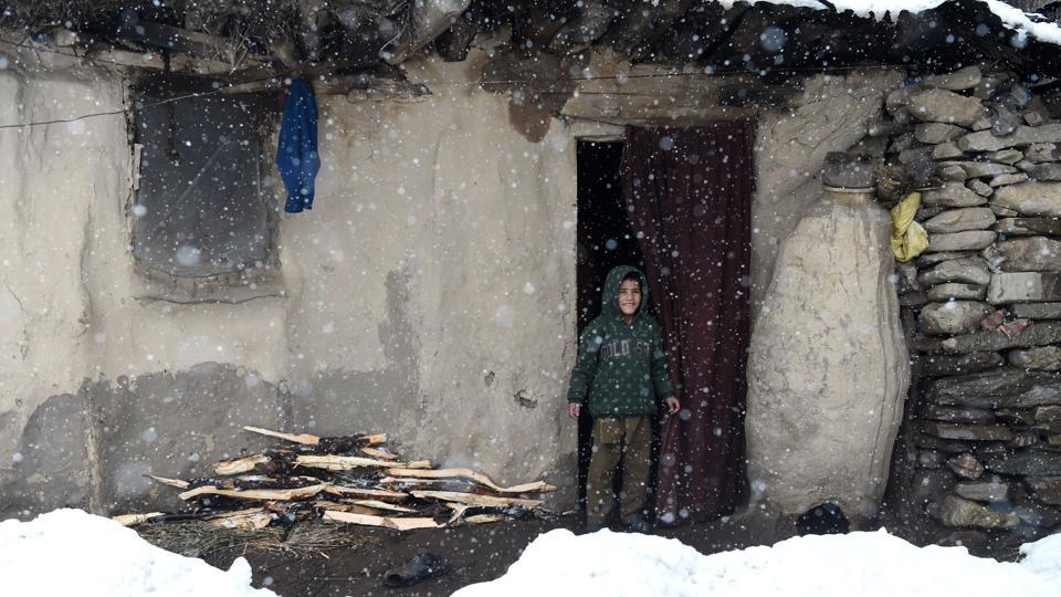 A Kashmiri boy looks on outside his mud house on the outskirts of Srinagar during a fresh snowfall on March 10, 2017.