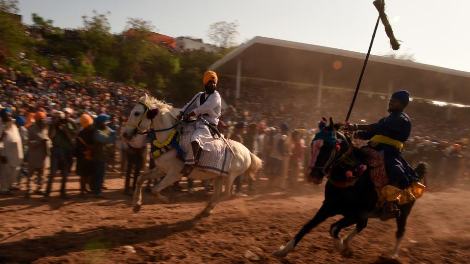 Nihangs ride their horses displaying tent pegging and other horse riding. The Hola Mohalla celebrations made its beginning around 1701 as Guru Gobind Singh wanted his troops to have mock battles to keep them battle-ready. (AFP)