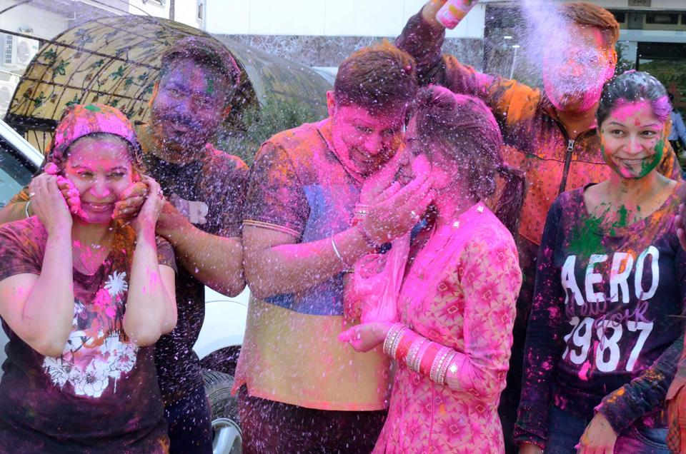 People smear colour on each other to celebrate Holi .