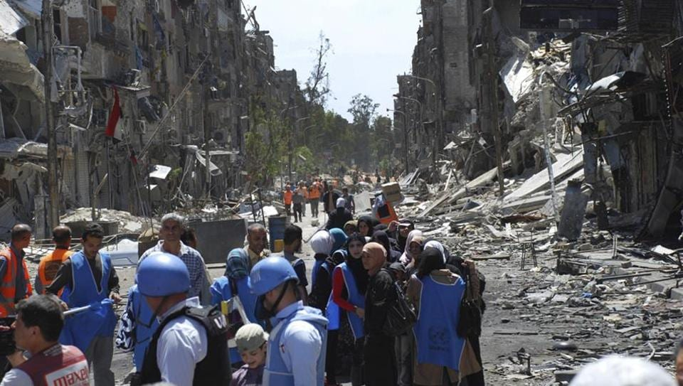 UN relief workers (in blue helmets and vests) wait to receive food aid on the southern edge of the Syrian capital Damascus, Syria, in May 2014. A new investigate report accuses the Syrian government of