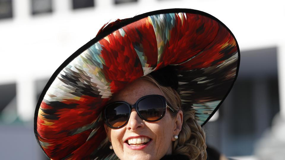 A racegoer wearing a flamboyant hat poses for photographers during Ladies' Day at Ascot (Stefan Wermuth  / REUTERS)
