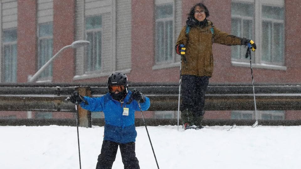 Harry Braunstien watches as his son Lucas skis during a snowstorm in the Brooklyn borough of New York City, U.S. (Brendan McDermid/REUTERS)