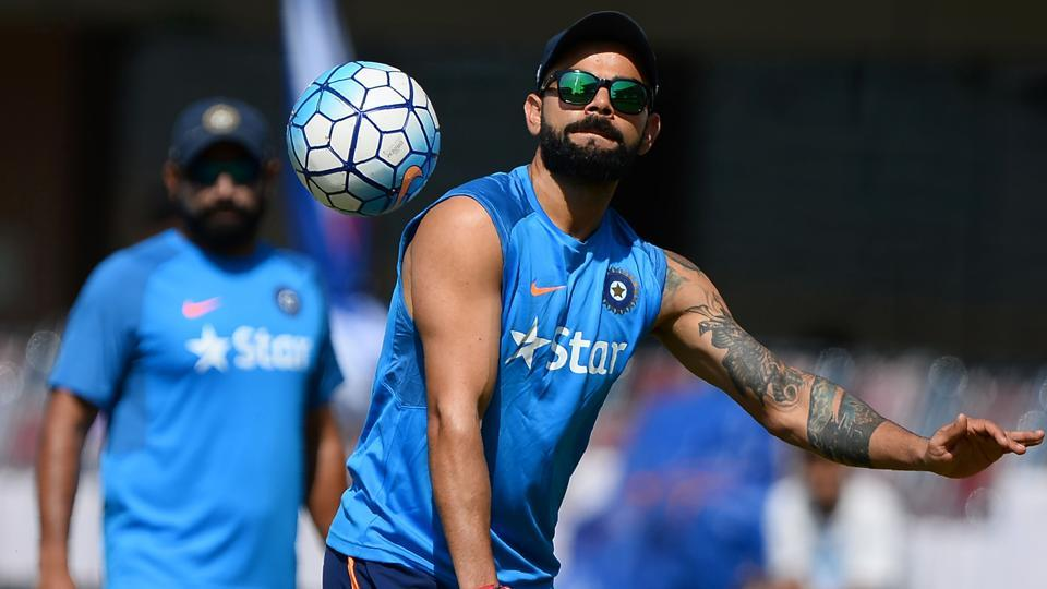 Virat Kohli (R) plays football with Indian cricket teammates during a training session ahead of the third Test against Australia in Ranchi.
