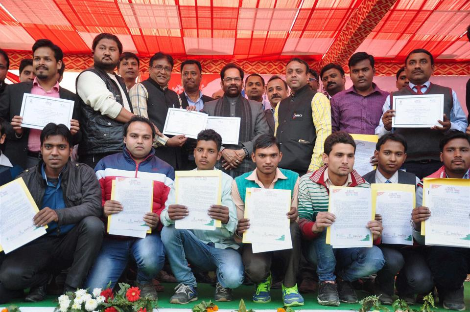 MoS for Parliamentary Affairs Mukhtar Abbas Naqvi poses for a group photo after giving apponitment letters during a Rozgar Mela in Moradabad on Sunday.