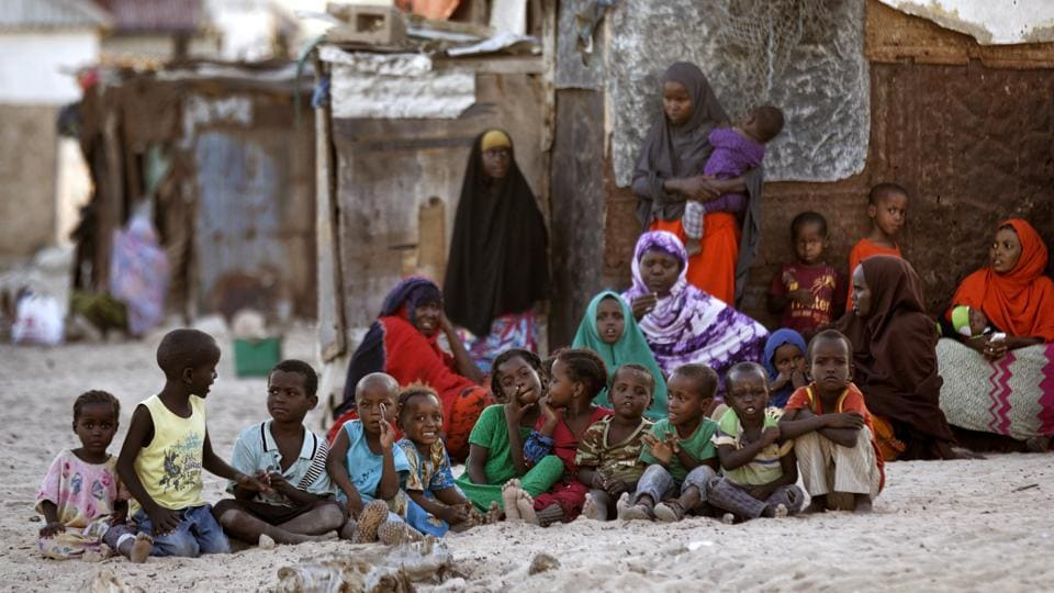Somali women and children gather at dusk on a sandy street in the former pirate village of Eyl, in Somalia. Some of the former pirates had quit as the international pressure grew and armed guards appeared on cargo ships. They turned to fishing but now say they're the ones being targeted at sea. (Ben Curtis/AP)