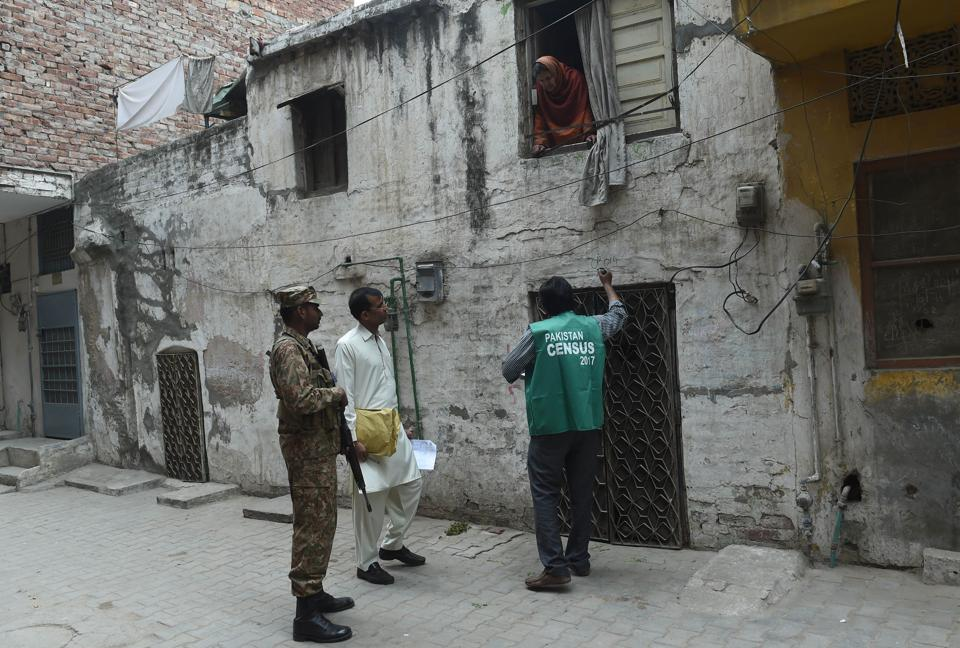 An official from the Pakistan Bureau of Statistics collects information from a resident as an army soldier stands guard in Lahore. Pakistan began its first census in almost two decades on Wednesday.