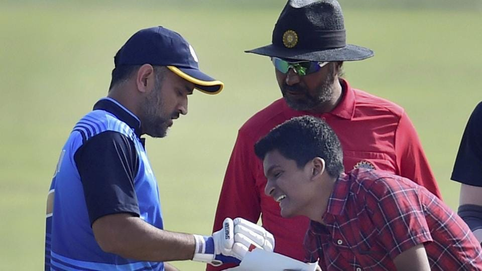 Jharkhand cricket team captain MS Dhoni obliges a young fan during the Vijay Hazare trophy quarterfinal match against Viharbha cricket team in New Delhi on Wednesday.