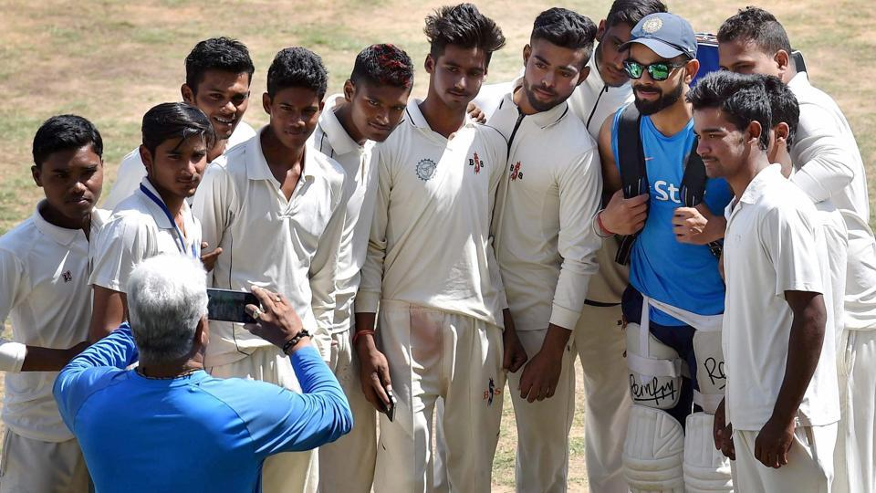 India cricket team skipper Virat Kohli poses for a photograph with young cricketers who worked with the team during the nets session in Ranchi onWednesday. India will play Australia cricket team in the third Test of the four-match series at MSDhoni's home town from Thursday. With the series tied 1-1 it's a must-win match for both the teams. (PTI)
