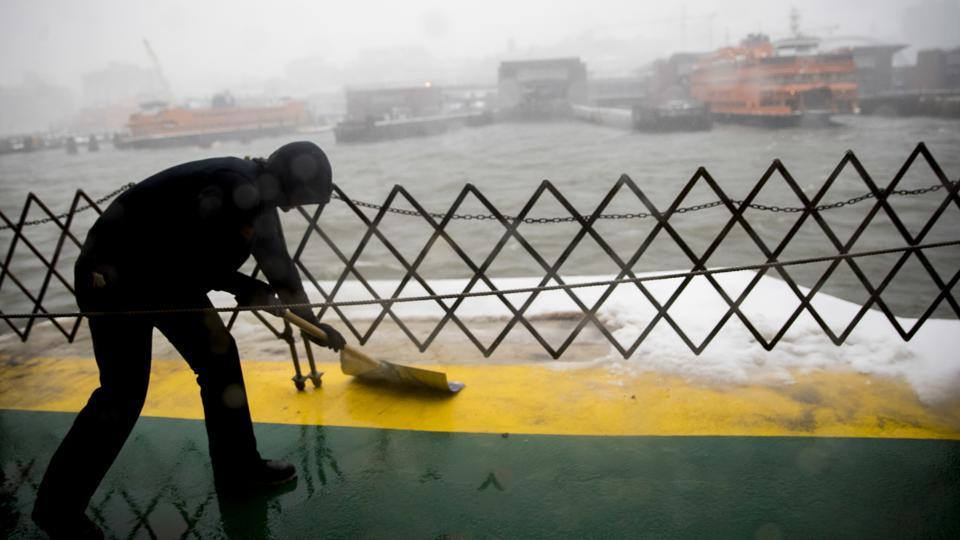 A member of the Staten Island ferry crew clears the deck as the ferry approaches the terminal during a snowstorm. (Mary Altaffer/AP)