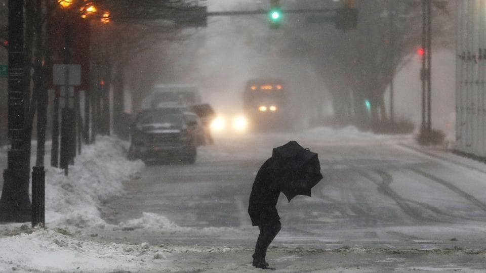 A person hunches while walking against strong winds in Jersey City, during a snowstorm. (Julio Cortez/AP)