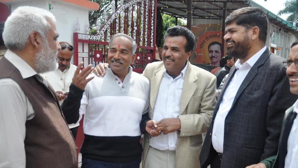 BJP leaders share a joke outside the party office in Dehradun on Thursday.