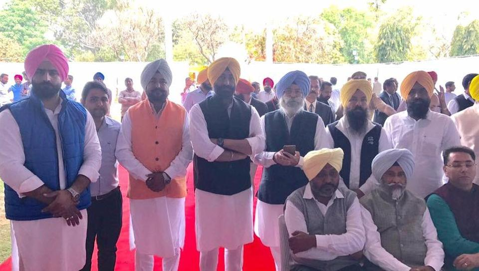 Some AAP MLAs standing at Capt Amarinder Singh's swearing-in as Punjab CM in Chandigarh on Thursday.