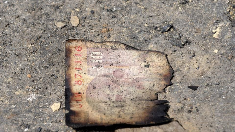 Half burnt ten rupee note  lies on the ground after  massive fire broke out at Sector 78 Noida.