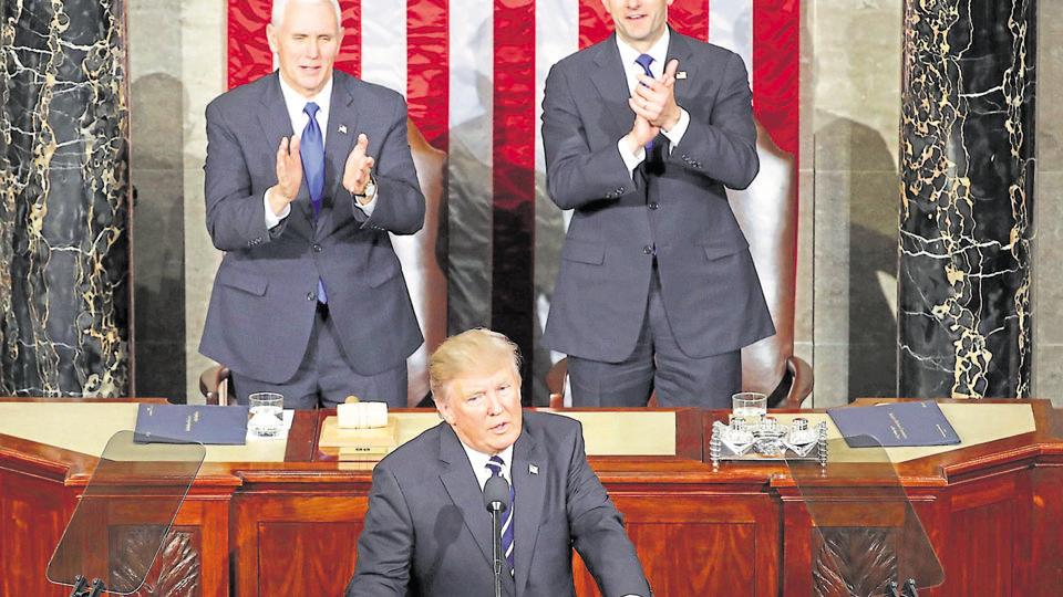 US President Donald Trump addresses a joint session of the US Congress as Mike Pence (left) and House Speaker Paul Ryan look on.