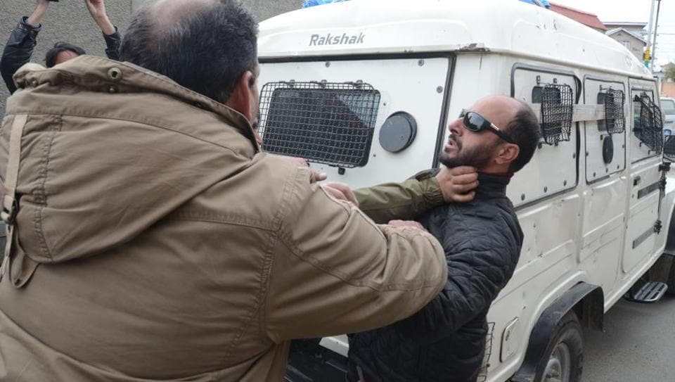 A policeman grabs AFP photographer Tauseef Mustafa by the throat outside Hurriyat Conference chairman Syed Ali Geelani's residence at Hyderpora, Srinagar, on Thursday.