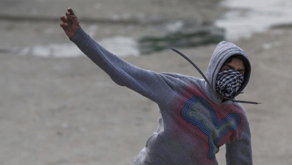 A protester throws a rock at Indian paramilitary soldiers in Srinagar, February 17, 2017